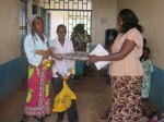 Lab Technician, Justine Nafula, handing out Christmas goodies to one of the poorest families